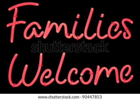 Neon signage stating that families are welcome on a black background