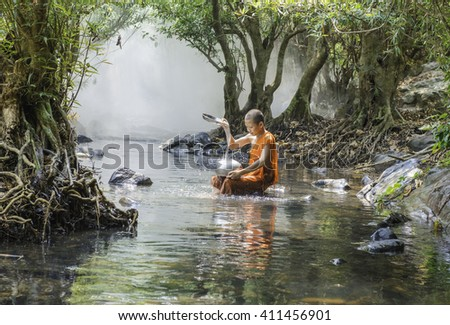 Neophyte is washing his container at river. Sangkhom, Nong khai, Thailand.