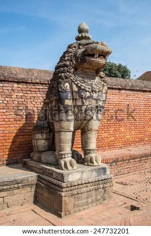 NEPAL, BHAKTAPUR, DURBAR SQUARE - NOVEMBER, 2014: Traditional ancient stone statue of lion - stock photo