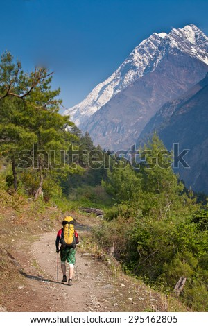 Nepal - man on hiking trail in mountains. Background - mountain lodge and snow peak - stock photo