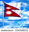 Nepal waving flag against blue sky - stock photo