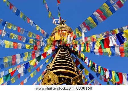 nepalese stupa with colorful prayer flags and clear blue sky - stock photo