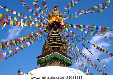 Nepalese stupa with prayer flagson a background of the blue sky.