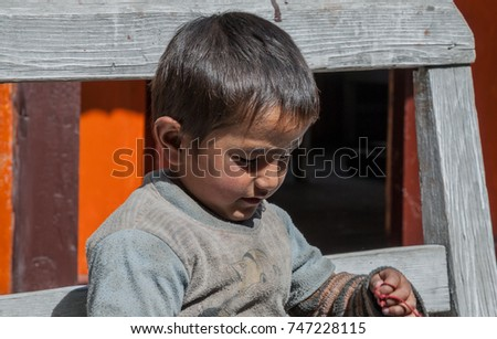 Nepali boy on Annapurna Circuit trek-October 7, 2008: A cute & lovely young kid  sitting on the porch of his home in Pisang village, Manang district, Gandaki zone, Nepal