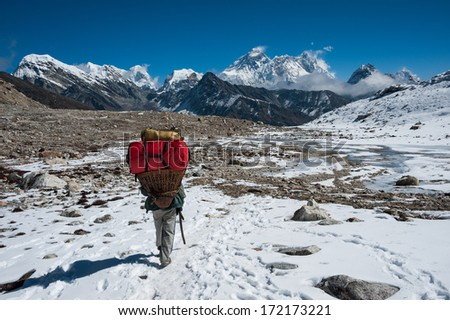 Nepali porter carrying heavy loads from Renjo pass with Mt.Everest in the background, Nepal. - stock photo