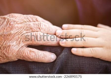 nephew touching grandfather's hand - stock photo