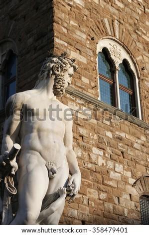 Neptune Fountain Statue at the Piazza della Signoria, Florence with the Palazzo Vecchio in the background - stock photo