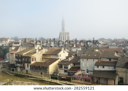 Nerac is the ancient French town lying on both sides of the Baise River. There are medieval townhouses and the cathedral in the winter mist.