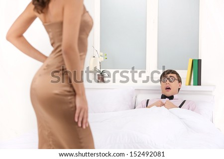 Nerd and beauty. Scared nerd man lying on the bed and looking at beautiful woman in dress - stock photo