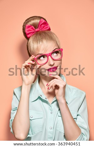 Nerd beauty fashion woman in stylish glasses thinking, idea. Attractive funny blonde girl think. Nerd with pinup hairstyle bow, fashion makeup. Unusual playful, thinking expression.Vintage, on pink