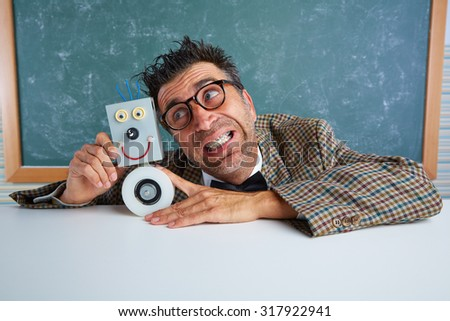 Nerd electronics technician with self made robot silly retro teacher - stock photo
