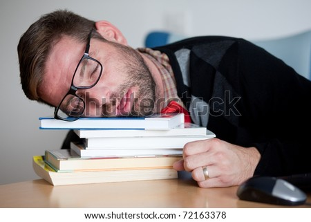 Nerd exhausted from studying. He fell asleep on a stack of books. - stock photo