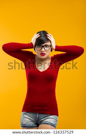 Nerd girl angry with something, aganist a yellow background - stock photo