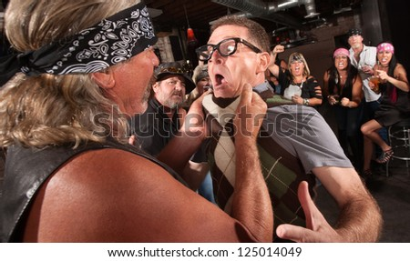 Nerd grabbed by collar in bar fight with tough gang member - stock photo
