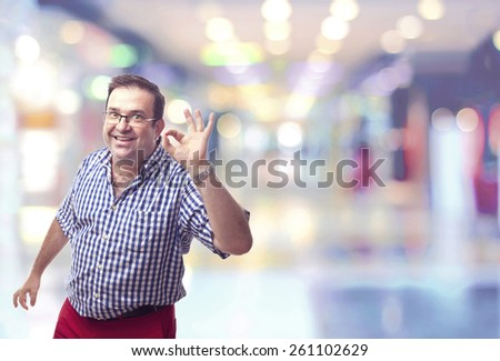 nerd man okay gesture in a shopping center - stock photo