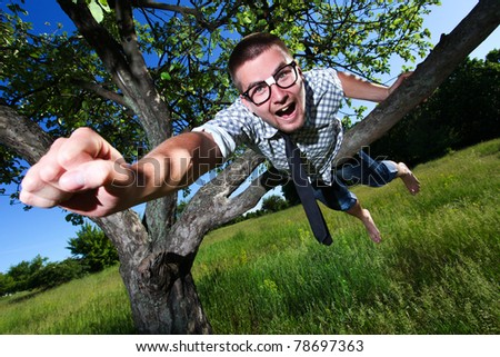 Nerd man thinking that he is superhero on the tree - stock photo