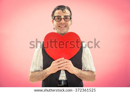 Nerd man with glasses happy for love heart on pink for valentine day - stock photo
