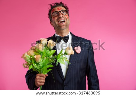 Nerd man with lipstick marks on face in Valentines Day and flowers