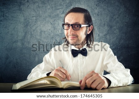 Nerd poet writing poems, sitting at work desk. - stock photo