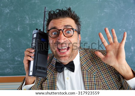 Nerd silly private investigator with retro walkie talkie on teacher bLAckboard - stock photo