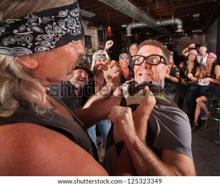Nerd threatening tough gang member grabbing him by the collar - stock photo