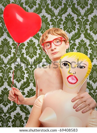 Nerd with blow-up doll - stock photo