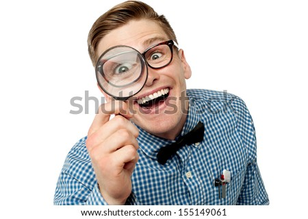 Nerd with magnifying glass in front of his eye - stock photo