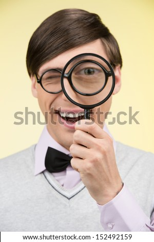 Nerd with magnifying glass. Young nerd man holding magnifying glass in front of his eye while standing against yellow background