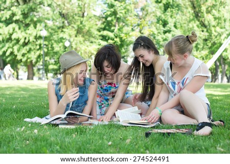 Nerds reading in the park - stock photo