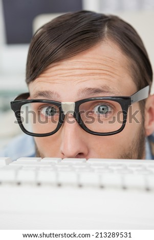 Nerdy businessman working on computer in his office