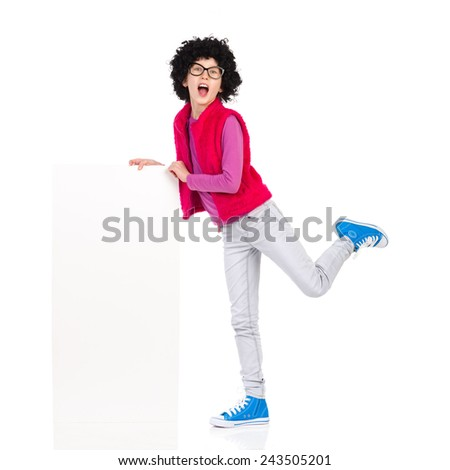 Nerdy girl posing with a placard. Funny girl in curly wig and black glasses standing on one leg close to white placard and shouting. Full length studio shot isolated on white. - stock photo