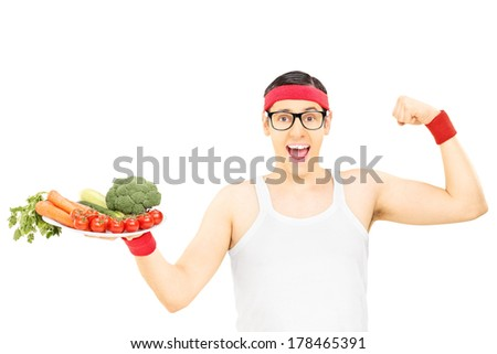 Nerdy guy holding plate with vegetables and showing muscle isolated on white background - stock photo