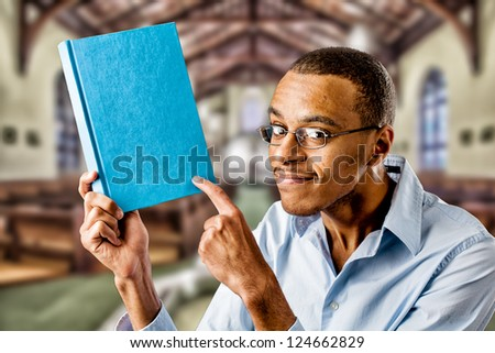 Nerdy looking black african american holding a book - stock photo