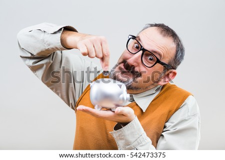 Nerdy man is putting coin into piggy bank.Money saving for nerdy man