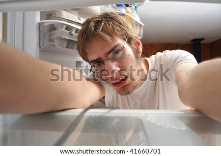 Nerdy Man looking for food in refrigerator - stock photo
