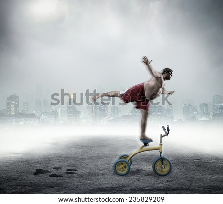 Nerdy man standing on a small bicycle