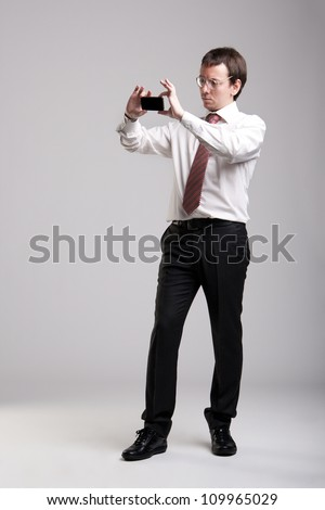 Nerdy manager taking pictures with his smartphone - stock photo