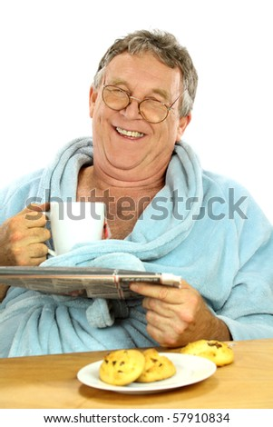 Nerdy middle aged man smiling while having breakfast and reading the paper.