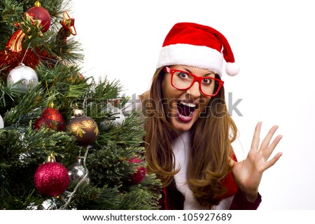 Nerdy Mrs Santa jumping out from behind a big christmas tree, huge smile for surprise