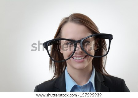 Nerdy office woman wearing silly funny large glasses - stock photo