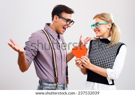 Nerdy woman is about to give a red heart  to her  boyfriend to show that she loves only him,My hearts belongs to you! - stock photo