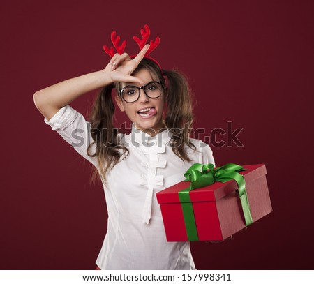 Nerdy woman with christmas gift showing loser sign - stock photo
