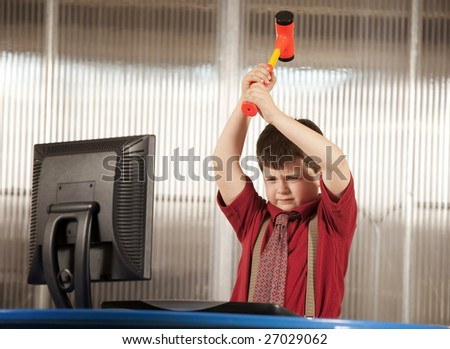 Nerdy young boy smashing his computer with a hammer - stock photo