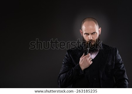 Nervous bearded man holding a pipe in his mouth. He is dressed in old-fashioned suit. Gray background.