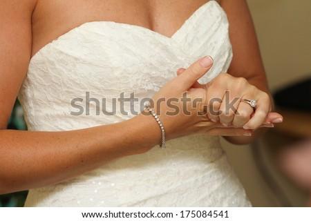 Nervous bride close up clutching hands - stock photo