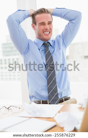 Nervous businessman with hands on head in his office - stock photo