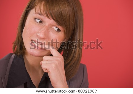 nervous businesswoman biting her nails on red background - stock photo