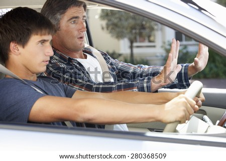 Nervous Father Teaching Teenage Son To Drive - stock photo