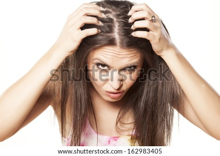 nervous girl looking in the mirror her scalp - stock photo