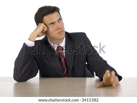 Nervous, handsome businessman. Seating behind desk. White background, front - stock photo